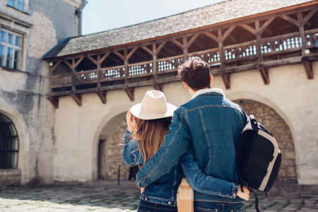 Couple of tourists walking in Olesko Castle yard admiring ancient architecture view. Travelling in Western Ukraine. Archivio Fotografico