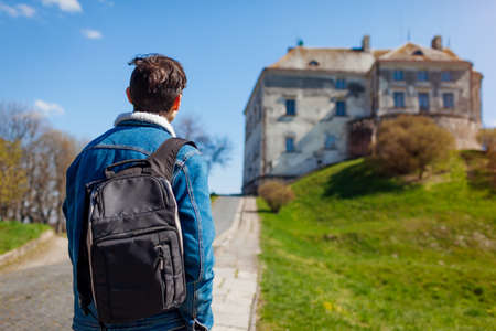 Tourist backpacker visiting Olesko Castle in spring. Trip to Western Ukraine. Traveler enjoys landscape and ancient architecture view Archivio Fotografico