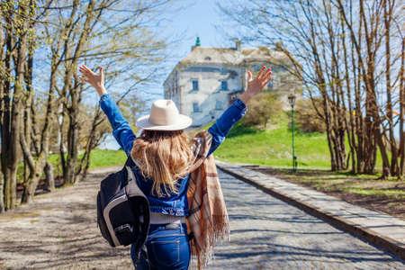 Happy tourist woman visiting Olesko Castle raising arms admiring architecture. Travelling in Western Ukraine. Spring trip Archivio Fotografico