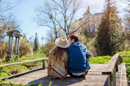 Loving couple of tourists relaxing by Olesko Castle in spring garden sitting on bridge enjoying view. Travelling in Western Ukraine.