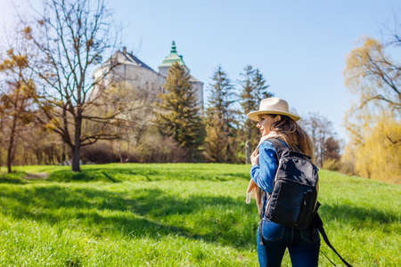 Tourist packpacker walking in Olesko Castle garden. Ancient architecture landmarks in Western Ukraine. Traveling among historic places