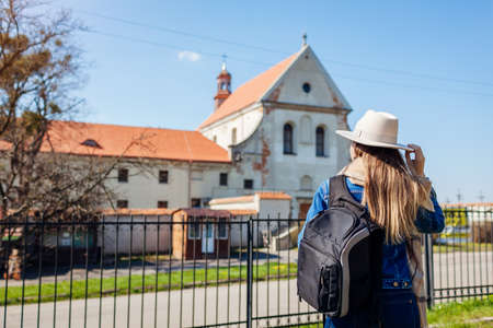 Tourist enjoys view of Capuchin monastery in Olesko, Lviv region, western Ukraine by Olesko Castle. Traveling to ancient architecture and historic places in spring