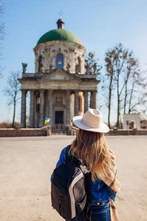 Tourist looking at ancient Roman Catholic church of saint Joseph in Pidhirtsi, Ukraine. Visiting ancient architecture landmarks and historic places