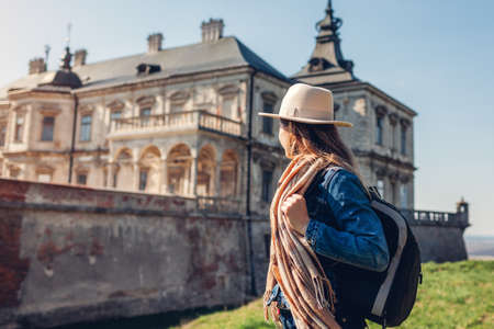 Tourist woman enjoys view of castle in Pidhirtsi. Travel to historic places of interest, ancient architecture and landmarks in Western Ukraine.