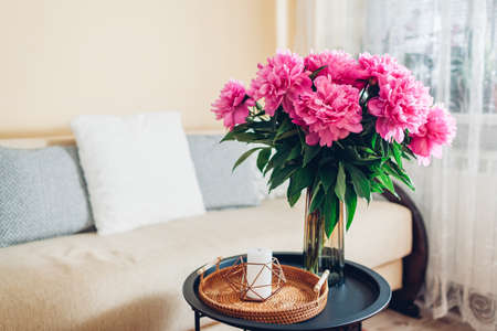 Interior and home decor. Fresh pink peonies flowers put in vase in living room by couch. Bouquet of blooms on coffee table