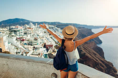 Woman tourist raised arms looking at Caldera sea landscape in Fira, Santorini island. Traveling during summer vacation