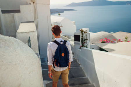 Santorini traveler man walking along narrow street in Fira, Greece enjoying sea view. Tourism, summer vacation Archivio Fotografico