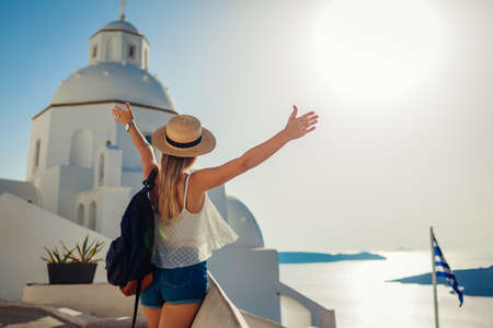 Woman tourist raised arms looking at Caldera sea landscape in Fira, Santorini island walking by traditional church.