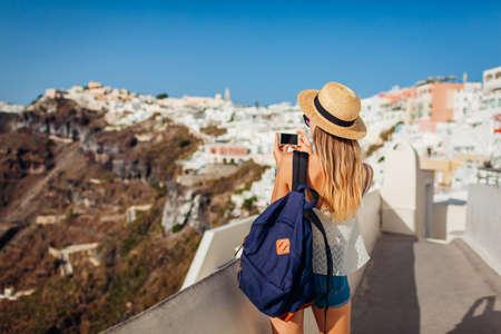 Santorini traveler woman taking photo of Thera, Fira village architecture on phone. Tourism, traveling, summer vacation