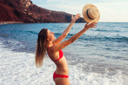 Young woman in bikini plays with hat relaxing on Red beach on Santorini, Greece. Girl enjoys sea and mountain landscape Archivio Fotografico