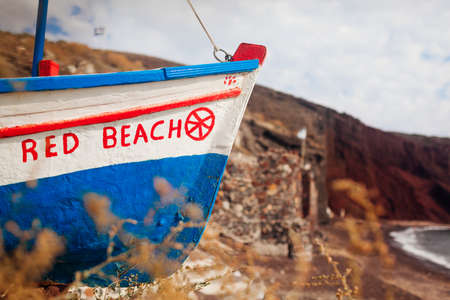 Boat with Red beach writing on Santorini island, Greece on seashore at summer. Close up
