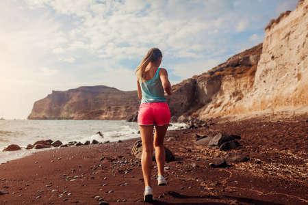 Woman running on Red beach on Santorini island. Female runner jogging during outdoor workout enjoying view