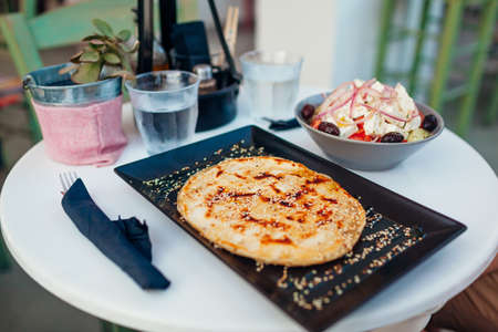 Greek soft pita, stuffed with cheese sprinkled with sesame seeds served with greek salad and water in cafe