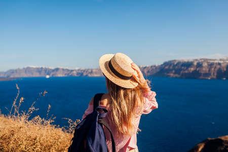 Traveler woman walking on Santorini island, Greece enjoying landscape. Happy hiker with backpack enjoys seaside Caldera view. Tourism