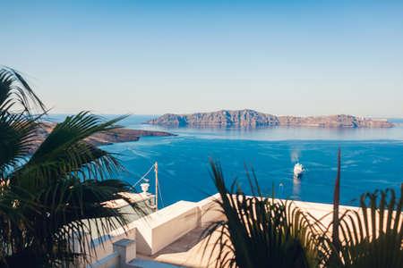 Landscape of Aegean sea with big passenger cruise ship near volcano on island of Santorini, Greece. Caldera view through palm trees. Tholos Naftilos