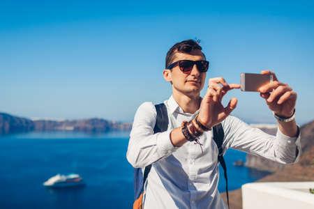 Santorini traveler man taking selfie with Caldera from Fira, Greece on smartphone. Tourist admiring Aegean sea landscape. Tourism, traveling, summer vacation concept. Archivio Fotografico