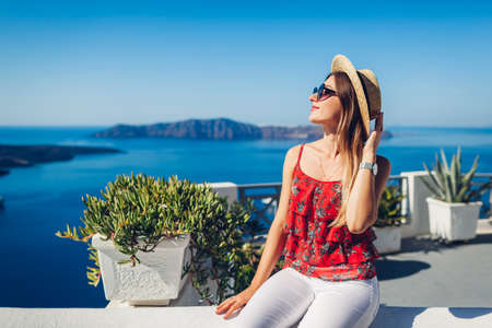 Woman traveler looking at Caldera landscape from Thera, Santorini island, Greece. Tourism, traveling, summer vacation