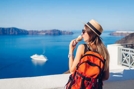 Woman traveler eating ice-cream in Fira Santorini island on Caldera sea background enjoying landscape. Summer vacation food.