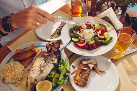 Man eats fish with vegetables and greek salad in outdoors restaurant. Fresh seafood dinner served. Close up top view of food