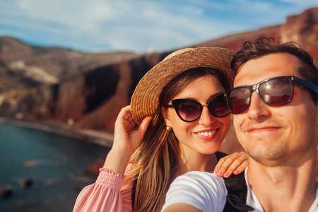 Loving couple takes selfie enjoying honeymoon on Red beach on Santorini island, Greece. Summer vacation. Traveling Archivio Fotografico