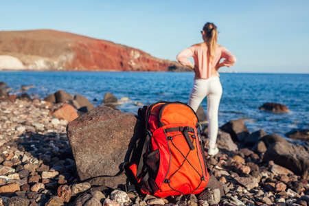 Hiker woman with backpack walking on Red beach on Santorini island, Greece enjoying sea and mountain landscape. Traveling and summer vacation