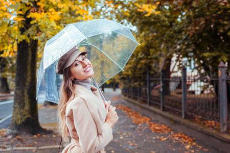 Happy young woman walking outdoors under transparent umbrella during rain. Fall season activities. Stylish girl enjoys weather