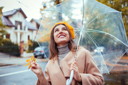 Happy young woman walking outdoors under transparent umbrella during rain holding yellow leaves. Stylish girl wearing warm clothes and accessories. Fall season weather