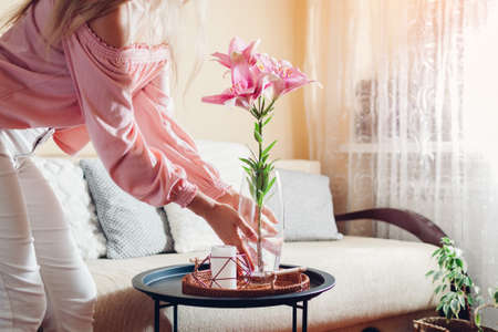 Woman puts vase with pink lily flowers on table. Housewife taking care of coziness at home. Interior and summer decor Archivio Fotografico