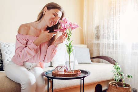 Woman smelling pink lily flowers in vase at home. Young model enjoys bouquet of fresh blooms. Interior and decor of living room