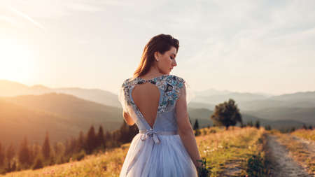 Beautiful bride in blue wedding dress with embroidery and bare back walking in mountains at sunset. Archivio Fotografico