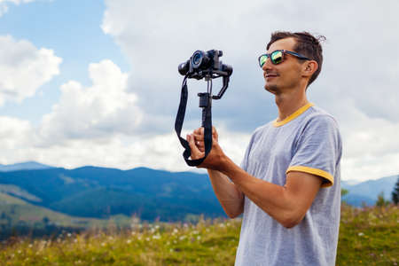 Videographer filming Carpathian mountains landscape. Man using steadicam and camera to make footage. Video shoot