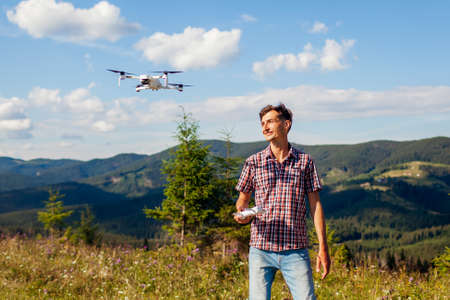 Aerial drone footage shooting of summer Carpathins. Man operating copter controller in mountains. Tourist filming nature