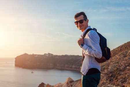 Tourist hiker walking by White beach on Aegean sea Santorini island, Greece enjoying summer landscape. Man backpacker traveling. Vacation