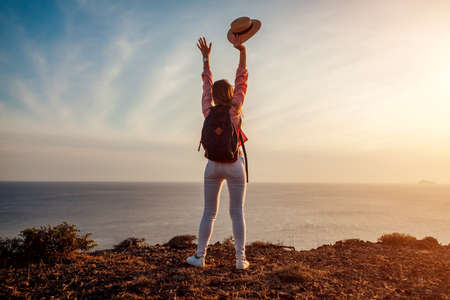 Traveler hiker reached mountain top on Santorini island, Greece enjoying sea landscape. Woman backpacker raised arms feeling happy. Summer tourism Archivio Fotografico