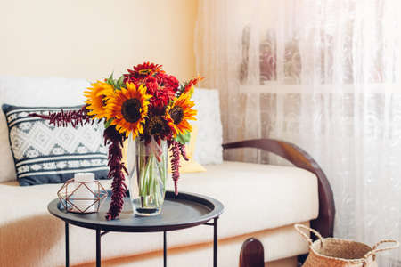 Bright bouquet of sunflowers and zinnia flowers put in vase in living room. Interior and home decor. Fall yellow red orange autumn blooms on table Archivio Fotografico