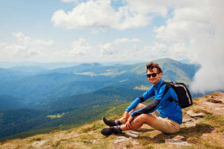 Trip to Carpathian mountains. Happy man hiker with backpack resting on top of Hoverla enjoying landscape. Traveling in summer Ukraine