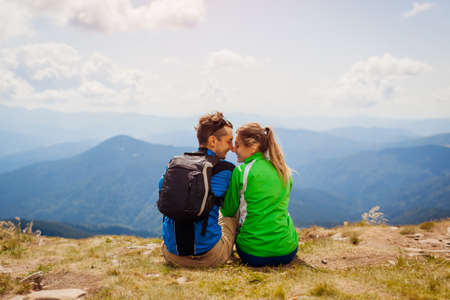 Couple of hikers admire view of Carpathian mountains. Happy tourists hug relaxing on top of Hoverla. Traveling in summer Ukraine