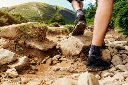 Hiking in Carpathian mountains. Close up of hiker's shoes. Man climbing on Hoverla walking on rocks . Traveling in summer Ukraine Archivio Fotografico