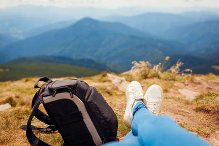 Hiking in Carpathian mountains. Hiker woman relaxing by backpack enjoying landscape. Traveling in summer Ukraine. Close up of shoes