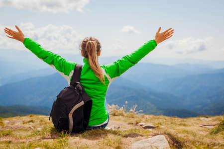 Trip to Carpathian mountains. Happy woman tourist hiker raising arms on top of Hoverla enjoying landscape. Traveling in summer Ukraine