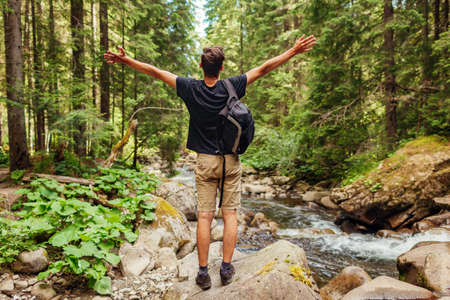 Traveler hiker with backpack raising arms by mountain river in Carpathian forest feeling happy. Man tourist enjoys landscape. Trip to summer Ukraine