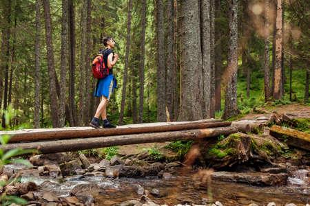 Traveler hiker with backpack crossing mountain river in Carpathian forest walking on wooden bridge. Man tourist enjoying landscape. Trip to summer Ukraine