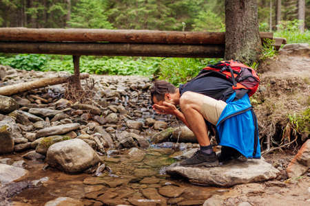 Traveler hiker with backpack washes face in mountain river in Carpathian forest by bridge. Tourist having rest by stream surrounded with summer nature Archivio Fotografico