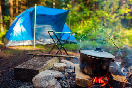 Camping in summer forest. Cooking on campfire in cauldron pot by hiking tent. Traveling and tourism