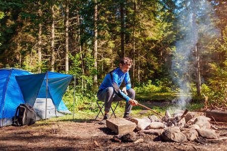Man relaxing by campfire in forest sitting next to tent. Summer camping. Traveling alone enjoying nature
