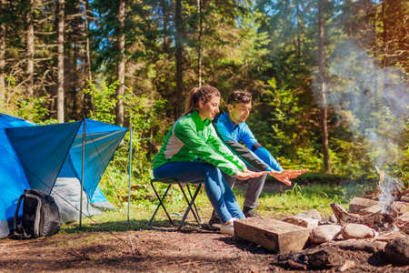 Young couple of travelers enjoy campfire in summer forest. Tourists sitting by tent warming hands. Man and woman relaxing camping in woods