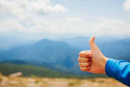 Man hiker giving thumb up on mountain landscape background. Active healthy sportive lifestyle. Close up. Traveling and tourism concept