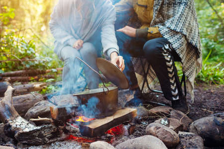Couple of travelers cooking on campfire in cauldron lifting pot lid checking food. Camping in summer forest. Traveling and tourism