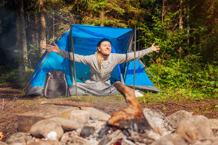 Happy young woman waking up in tent by campfire in summer forest. Traveler raising arms feeling good after night of camping. Archivio Fotografico