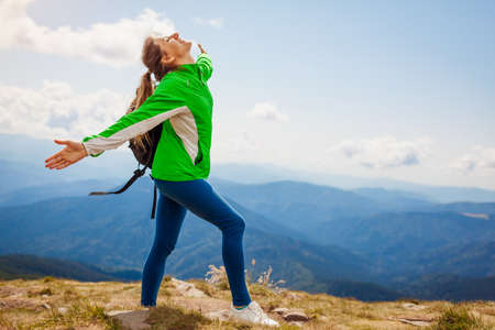 Trip to Carpathian mountains. Happy woman tourist hiker with backpack raising arms on top of Hoverla enjoying landscape and fresh air. Traveling in summer Ukraine
